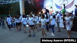 Дети из Казахстана, вернувшиеся из США, и волонтеры, работающие на фестивале, танцуют Cha-Cha Slide. Алматы, 5 августа 2016 года.