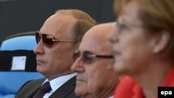 Уенны Русия президенты Владимир Путин (с), FIFA президенты Сепп Блаттер һәм Германия канцлеры Ангела Меркель карады