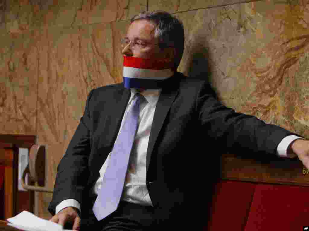 French Deputy Alain Dupont-Aignan protests by using a French flag as a gag during a speech of Prime Minister Francois Fillon on the French intervention in Libya at the National Assembly in Paris.Photo by Jacques Brinon for The AP
