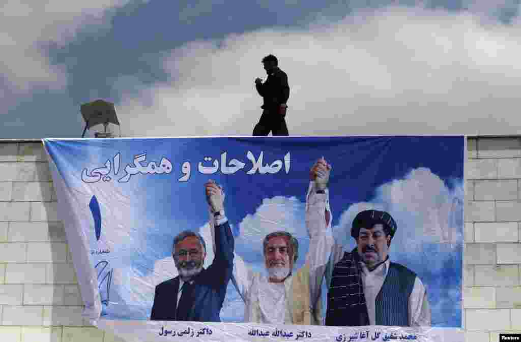 A man installs a banner for Afghan presidential candidate Abdullah Abdullah during the first day of the second round of the presidential election campaign in Kabul on May 22. (Reuters/Omar Sobhani)
