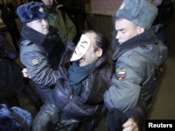 Russian police officers detain an activist during a copycat Occupy protest in central Moscow on November 7.