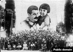Советтик тургундар Сталин менен Геля Маркизованын плакаттагы сүрөтүнүн жанында шаттана сүрөткө түшүүдө. Артек, Крым. 27.8.1937.