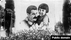 Советтик тургундар Сталин менен Геля Маркизованын плакаттагы сүрөтүнүн жанында сүрөткө түшүүдө. Артек, Крым. 27.8.1937.