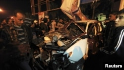 People look at the wreckage of a police car after an attack in Benghazi on January 14. At least one police officer was wounded when attackers threw a hand grenade at the patrol car in a series of assaults on security officials.