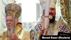 Вселенський патріарх Варфоломій (ліворуч) і глава Православної церкви України митрополит Епіфаній, який тримає томос про автокефалію. Стамбул, 6 січня 2019 року