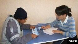"""""""Сана Сезім"""" үкіметтік емес ұйымының өкілі Шахноза Хасанова (оң жақта) Қазақстанда жұмыс істеп жүрген шетелдік азаматқа еңбек мигранттарының құқығы туралы кеңес беріп отыр. Шымкент, 10 ақпан 2009 жыл."""