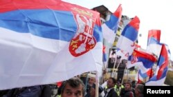 People wave Serbian flags during a rally in the ethnically divided town of Mitrovica, where local Serbs refuse to accept the independence declared by Kosovo's Albanian majority.