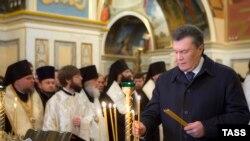 Президент Виктор Янукович Биримдик күнүнө карай чиркөөдө өткөрүлгөн зыяпатта шам койууда. Киев, 22-январь