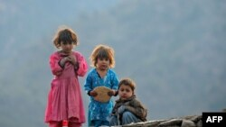 Copii afgani privind militari SUA în satul Shigal, provincia Kunar, Afganistan.