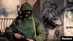 Ukraine -- An armed man stands near a Ukrainian military base in Simferopol, March 3, 2014