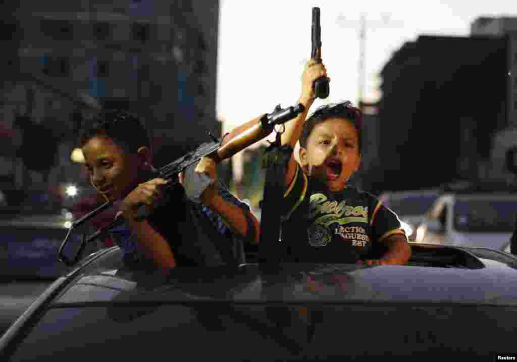 Palestinian children hold guns as they celebrate what they said was a victory over Israel following the declaration of a cease-fire in Gaza City on August 26. (Reuters/Suhaib Salem)