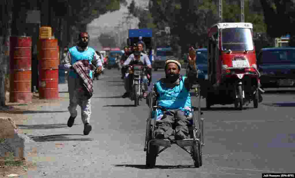 An Afghan man on a wheelchair joins on a Peace Walk as they leave on a journey by foot to Kabul to cover a distance of around 1,800 kilometers, calling for an end to decades of war, in Herat, on August 7. (EPA-EFE/Jalil Rezayee)