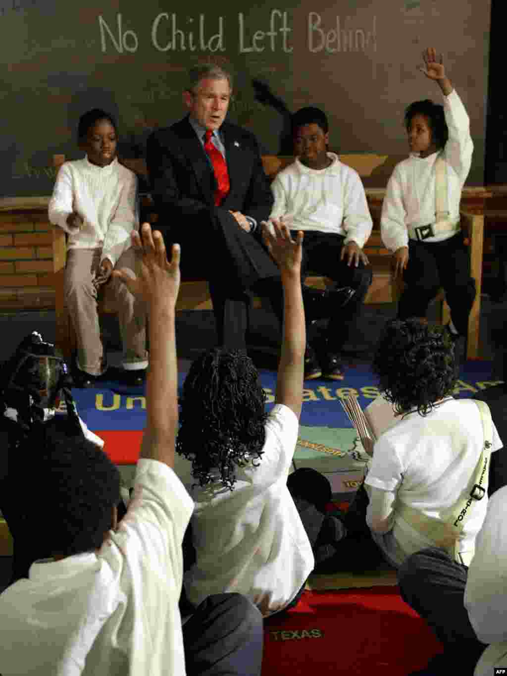 "'No Child Left Behind' education law - U.S. President George W. Bush sits with students Khadijah McCainn (left), Damien Goolsby (center), and Darlet Horton (right) as he talks to students on the anniversary of the ""No Child Left Behind Act"" on January 5, 2004, at Pierre Laclede Elementary School in St. Louis, Missouri."