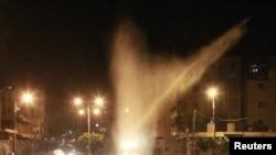 Таиз шаҳрида полиция намойишчилар устидан сув пуркамоқда.