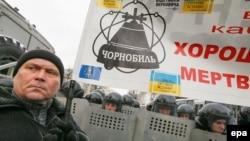 Один из протестующих в Киеве держит плакат с эмблемой Чернобыльской аварии. 14 января 2014 года.