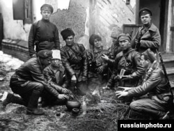 Red Army fighters gather for lunch around a fire in 1919.