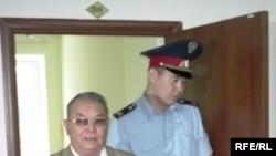 Полицейский выводит бывшего советника акима Западно-Казахстанской области Алпамыса Бектурганова в наручниках из зала суда. Уральск, 13 августа 2009 года.