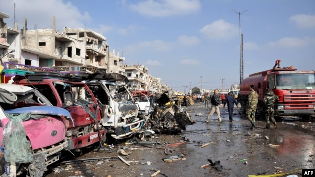 Damaged vehicles line the site of a double car-bomb attack in the Al-Zahraa neighborhood of the central Syrian city of Homs on February 21. More than 140 people killed in bombings in Damascus and Homs.