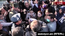 Opposition leader Nikol Pashinian tears up the police notification requiring the protesters to stop in Yerevan on April 17.