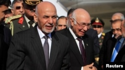 Afghan President Ashraf Ghani (L) walks with Sartaj Aziz, Pakistani national security adviser, after arriving Islamabad on November 14, 2014.