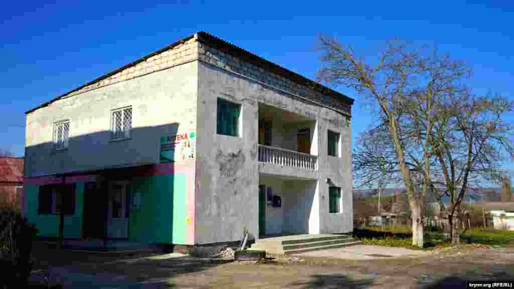 Здание в центре села, где на первом этаже размещены аптека и отделение почты, а на втором – библиотека.