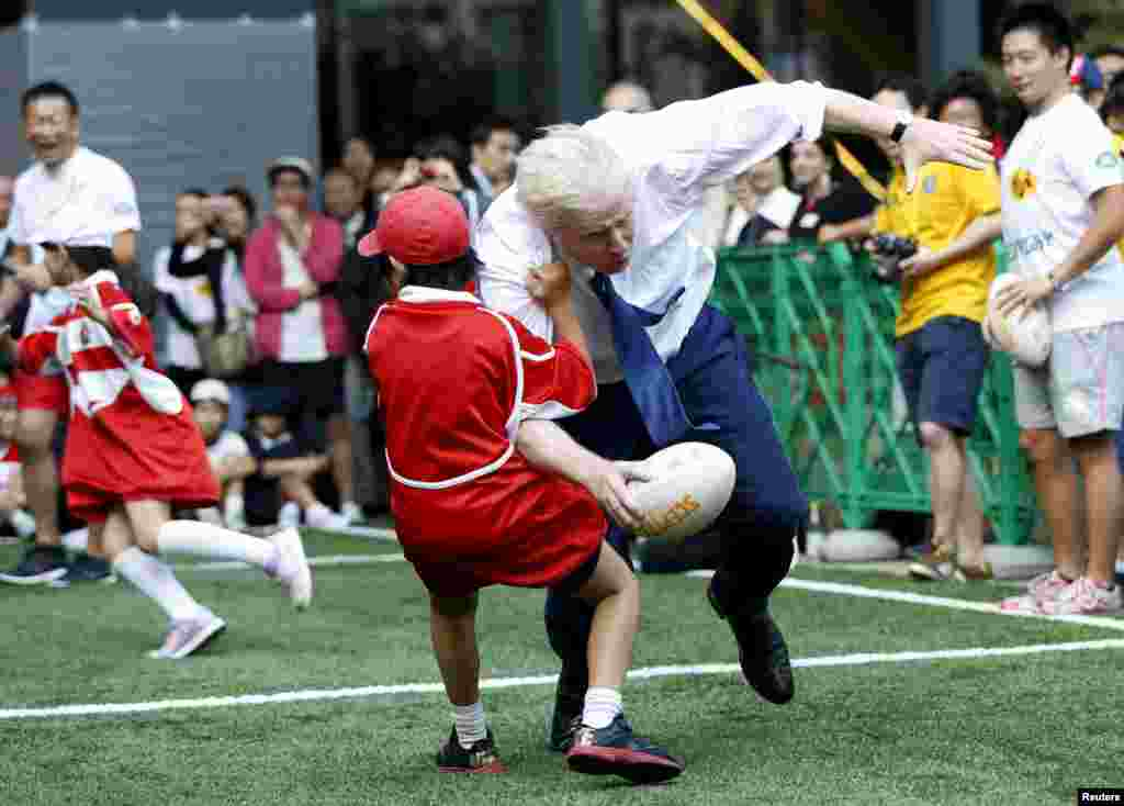 London Mayor Boris Johnson collides with 10-year-old Toki Sekiguchi during a game of street rugby with a group of Tokyo children while on a trade mission trip to Japan on October 15.(Reuters/Issei Kato)