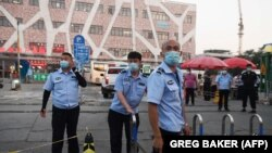 """""""Жаңа вирус ошағы"""" азық-түлік базарына баратын жолды жауып тұрған сақшылар. Пекин, 12 маусым 2020 жыл."""