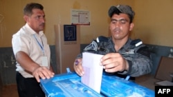 An Iraqi policeman casts his ballot in Fallujah, in Anbar Province, on June 17, as security forces vote early.