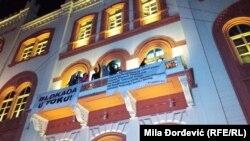 """Studenti koji od 13. septembra blokiraju zgradu Rektorata Univerziteta u Beogradu sa balkona pozdravljaju učesnike protesta """"1 od 5 miliona""""."""