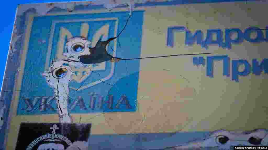 Розстріляна, вочевидь, із травматичної зброї державна символіка України на охоронній табличці