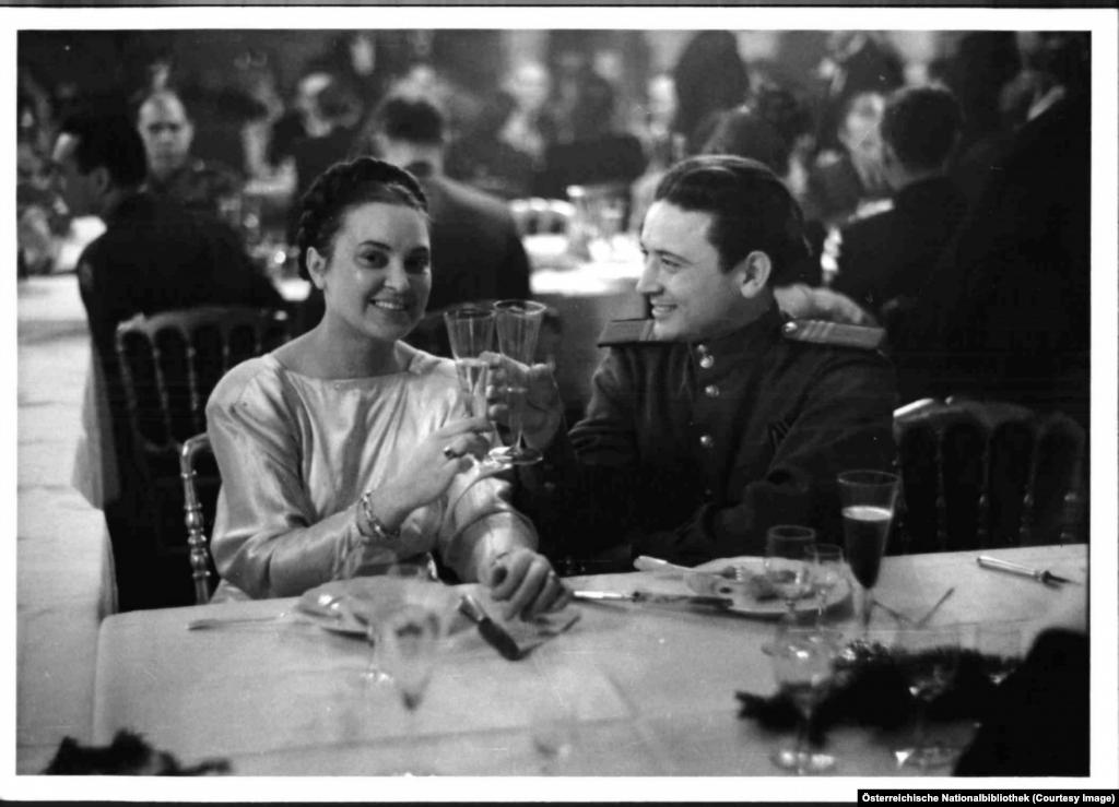 Съветски войник вдига наздравица с дама по време на празненство в двореца Хофбург.