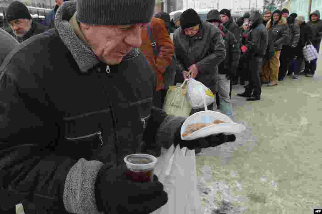 Homeless people line up for free hot food at a kiosk organized by social services in Kyiv.