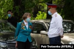 Женщина и сотрудник полиции у входа в парк имени 28 гвардейцев-панфиловцев. Алматы, 9 мая 2020 года.