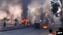 A video grab shows smoke billowing from burning tires and trash containers in the Al-Hajar Al-Aswad district of Damascus on July 18.