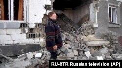 Žena stoji pored svoje kuće koja je oštećena u borbama ukrajinske vojske i proruskih separatista, 18. februar 2020.