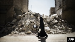 A Syrian woman walks past a destroyed building while walking to a food-distribution center in Aleppo.