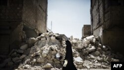 A Syrian woman walks past a destroyed building while reaching a food distribution centre in Aleppo earlier this month.