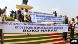 Нигерия мен Камерун азаматтары «Боко Харам» экстремистік тобына қарсы жазулар ұстап тұр. (Көрнекі сурет).