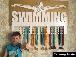 Школьник и пловец Никита Ковалёв на фоне своей медальницы.