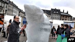 A WWF-sponsored artist carves an ice sculpture of a polar bear in Copenhagen to highlight the UN Climate Conference that is set to begin on December 7.
