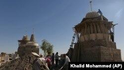 Disa irakianë duke rregulluar tempullin e tyre pasi është shkatërruar nga militantët e grupit ekstremist, Shteti Islamik, foto nga arkivi