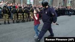 A Russian riot police officer detains a teenager during pension protests in St. Petersburg on September 9.