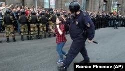 Полицейский задерживает подростка на митинге против пенсионной реформы в Санкт-Петербурге, 9 сентября 2018