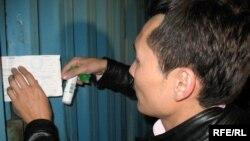 Қаржы полициясының қызметкері баспа есігіне мүлік тұтқындалғаны туралы қағаз жабыстырып жатыр. Алматы, 24 қыркүйек 2009 жыл. (Көрнекі сурет)