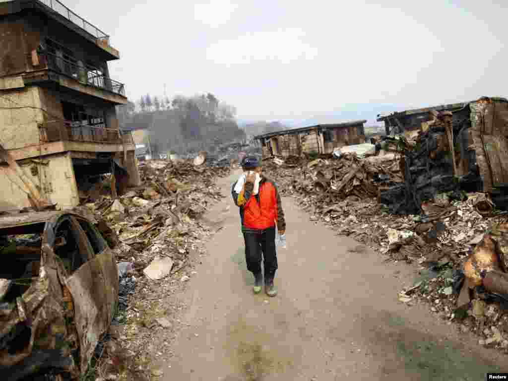 A man covers his face as he walks through a former residential area of Otsuchi on March 14