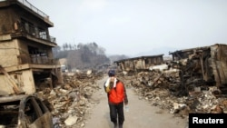 Japan -- A man covers his face as he walks through a destroyed residential area of tsunami-hit Otsuchi, 14Mar2011
