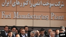 President Mahmud Ahmadinejad waves as he poses with officials outside Iran's fuel manufacturing plant during its inauguration ceremony.