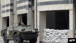 Syria -- An armored vehicle stands outside the sandbagged police headquarters of the central city of Homs, 30Aug2011