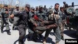 Полицейлер жарылыстан зардап шеккен адамды көтеріп барады. Кабул, 25 наурыз 2014 жыл.