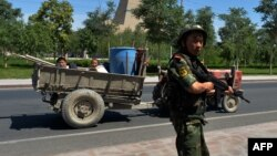 A Chinese paramilitary policeman mans a checkpoint on the road to the riot-affected Uyghur town of Lukqun in Xinjiang Province on June 28.